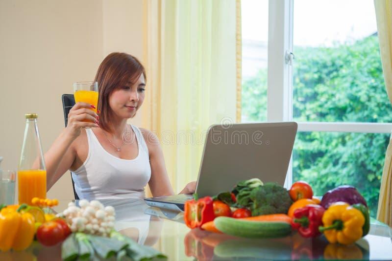 Giovane donna che beve il succo di arancia fotografie stock libere da diritti