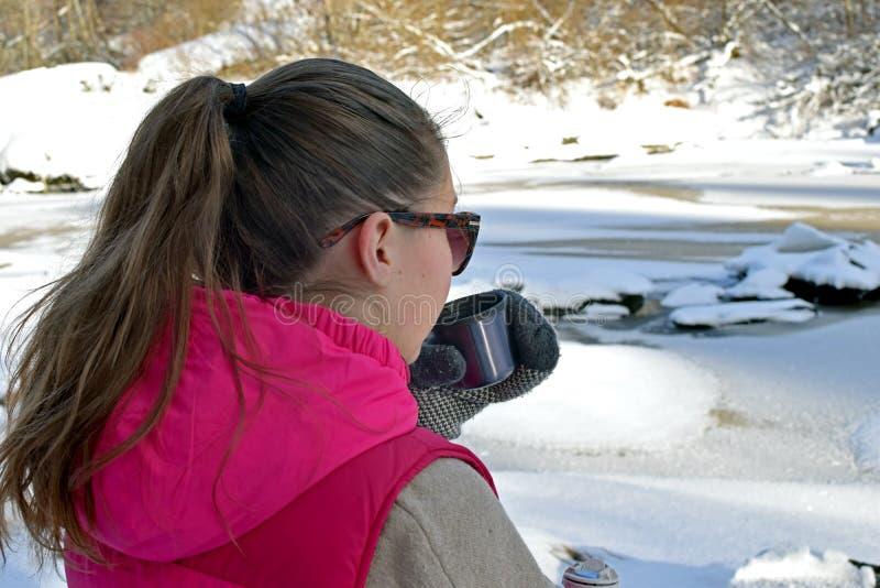 Giovane donna che beve tè caldo sulla foresta di inverno fotografia stock