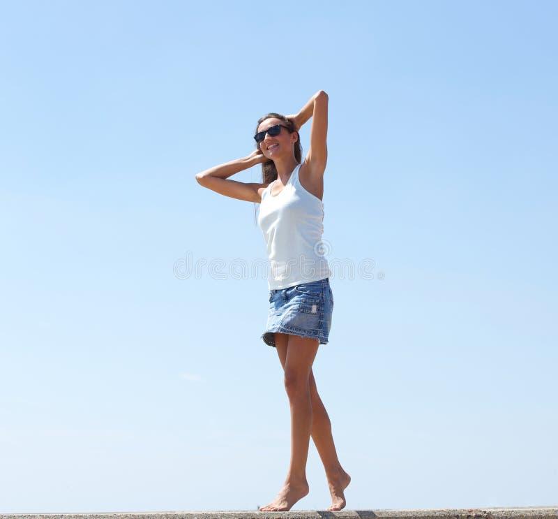 Giovane donna che cammina con la mano in capelli immagini stock libere da diritti