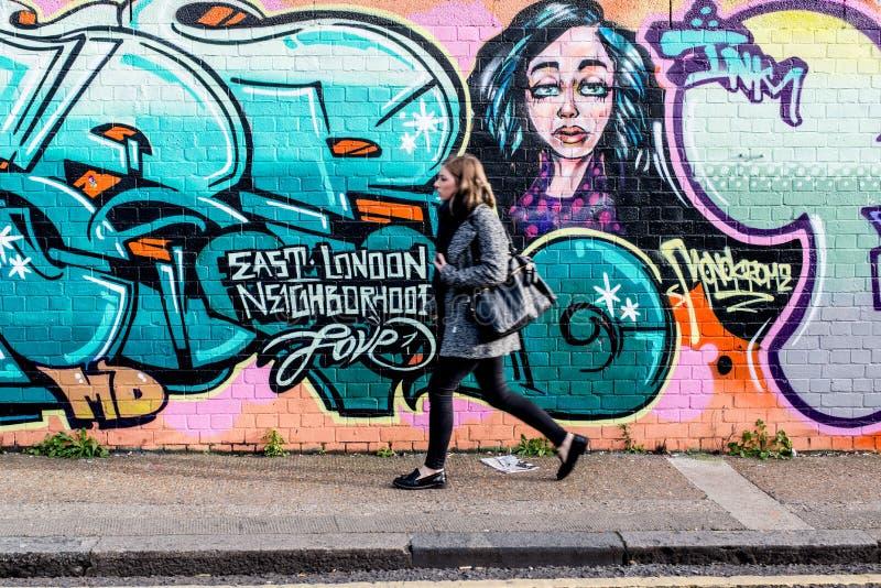 Giovane donna che cammina davanti ad una parete con i graffiti immagine stock