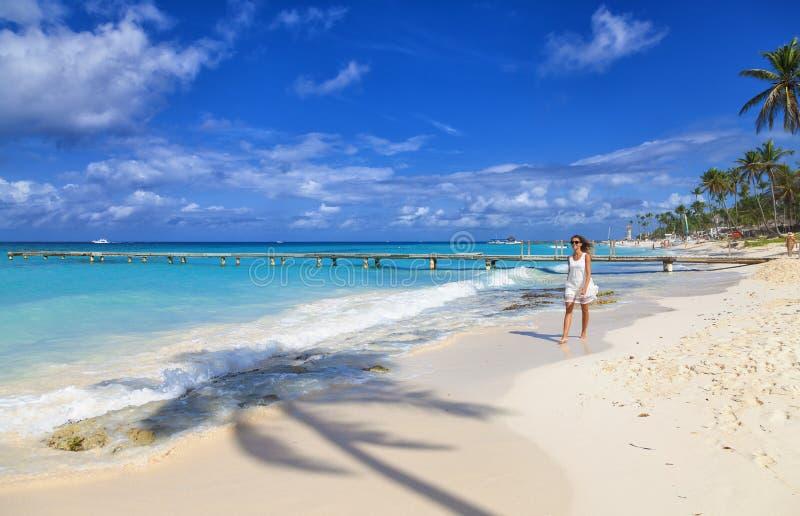 Giovane donna che cammina lungo la spiaggia tropicale della sabbia bianca fotografia stock libera da diritti