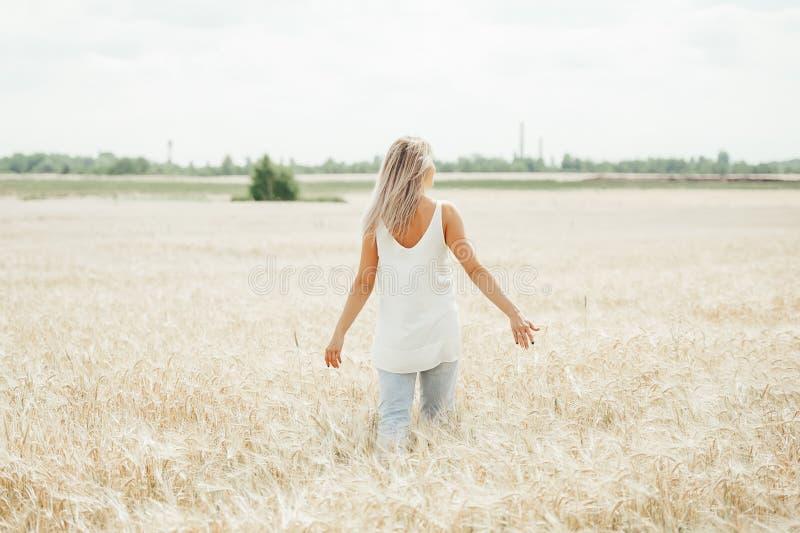 Giovane donna che cammina nel giacimento di grano Vista posteriore immagini stock