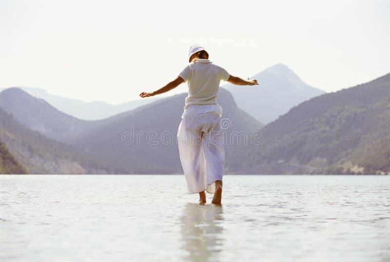 Giovane donna che cammina nel lago fotografia stock libera da diritti