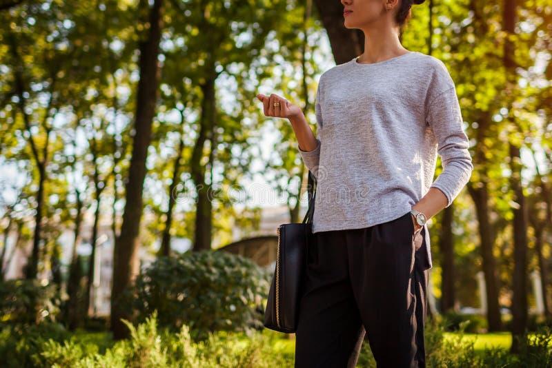 Giovane donna che cammina nel parco di estate Ragazza che indossa i vestiti e gli accessori alla moda fotografia stock