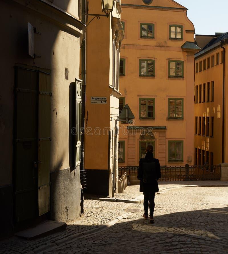 Giovane donna che cammina nella luce solare fotografie stock libere da diritti