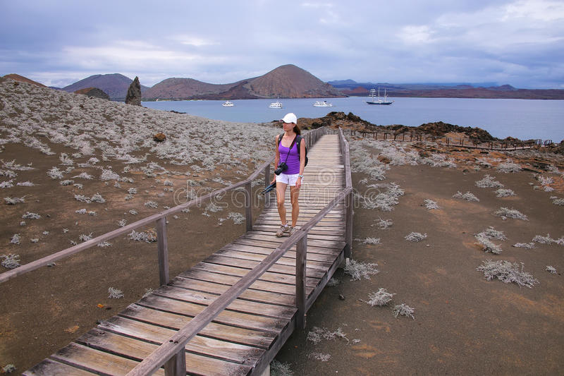 Giovane donna che cammina su un sentiero costiero sull'isola di Bartolome, Galapago fotografia stock