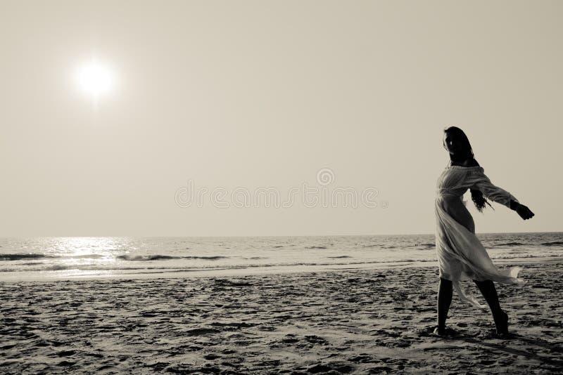 Giovane donna che cammina su una spiaggia fotografia stock libera da diritti