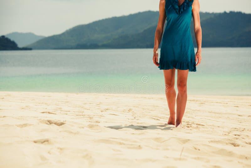 Giovane donna che cammina sulla spiaggia tropicale immagine stock libera da diritti