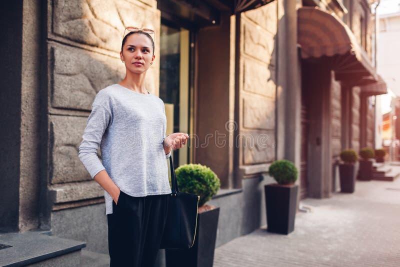 Giovane donna che cammina sulla via della città Ragazza che indossa i vestiti e gli accessori alla moda fotografia stock libera da diritti
