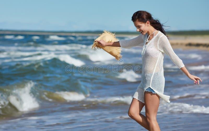 Giovane donna che cammina in vestito bianco d'uso dalla spiaggia dell'acqua immagini stock libere da diritti