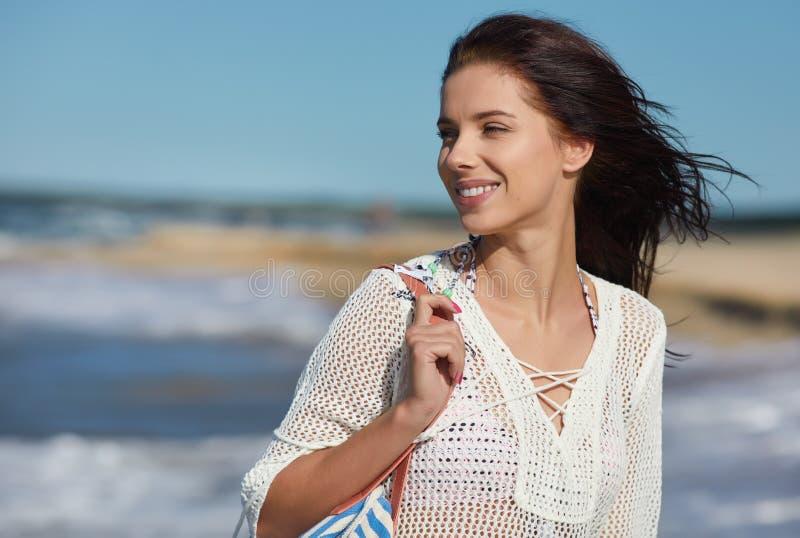 Giovane donna che cammina in vestito bianco d'uso dalla spiaggia dell'acqua immagine stock libera da diritti