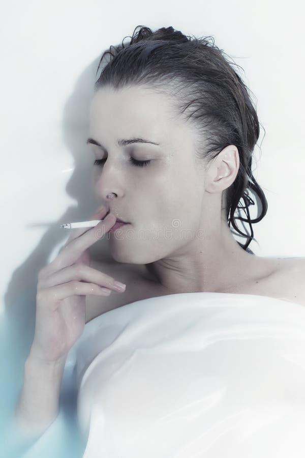Giovane donna che cattura un bagno con una sigaretta fotografie stock libere da diritti