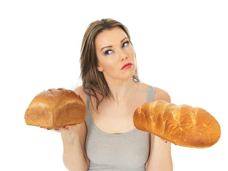 Giovane donna che confronta bianco e pane nero immagini stock libere da diritti