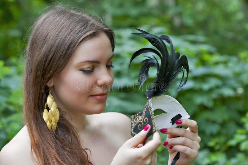 Giovane donna che considera la maschera veneziana di carnevale fotografia stock