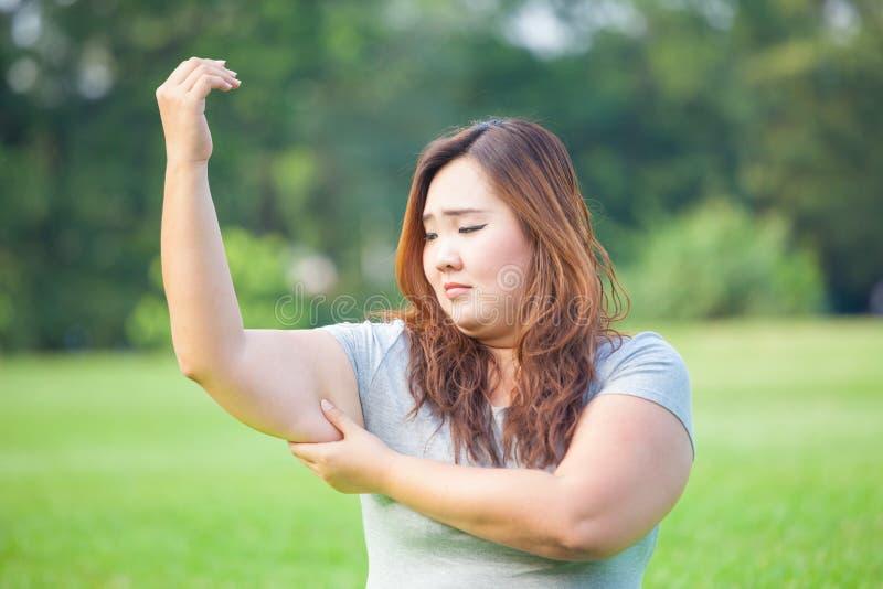 Giovane donna che controlla il suo grasso del braccio immagini stock libere da diritti
