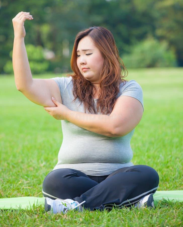 Giovane donna che controlla il suo grasso del braccio immagini stock