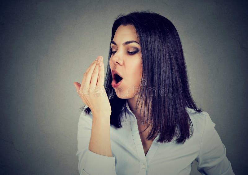 Giovane donna che controlla il suo respiro con la mano su fondo grigio fotografia stock libera da diritti