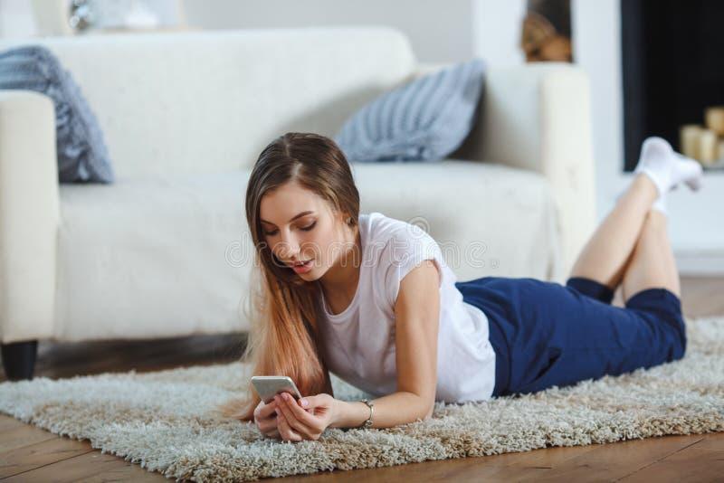 Giovane donna che controlla il suo Smart Phone che si trova sul tappeto fotografia stock