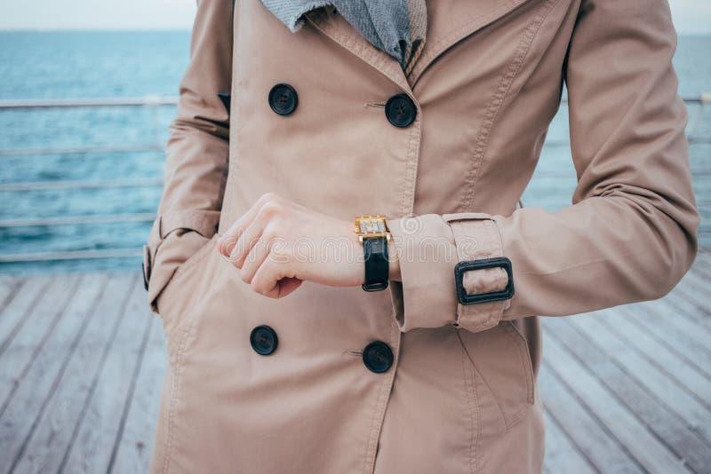 Giovane donna che controlla tempo sugli orologi immagine stock