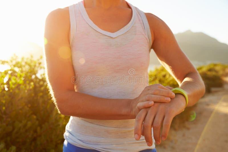 Giovane donna che controlla tempo sul suo orologio sportivo fotografie stock