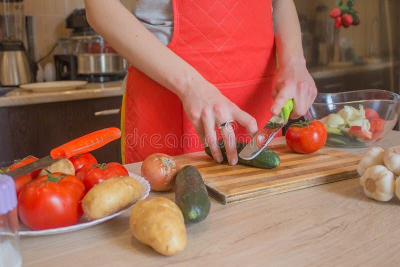 Giovane donna che cucina pasto sano nella cucina Cucinando alimento sano a casa Donna in cucina che prepara le verdure Tagli del  fotografia stock
