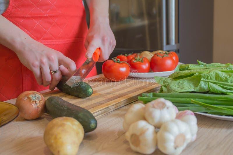 Giovane donna che cucina pasto sano nella cucina Cucinando alimento sano a casa Donna in cucina che prepara le verdure Tagli del  immagini stock