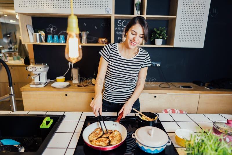 Giovane donna che cucina un pasto sano in cucina domestica Facendo cena sulla fresa facente una pausa di induzione dell'isola di  immagine stock