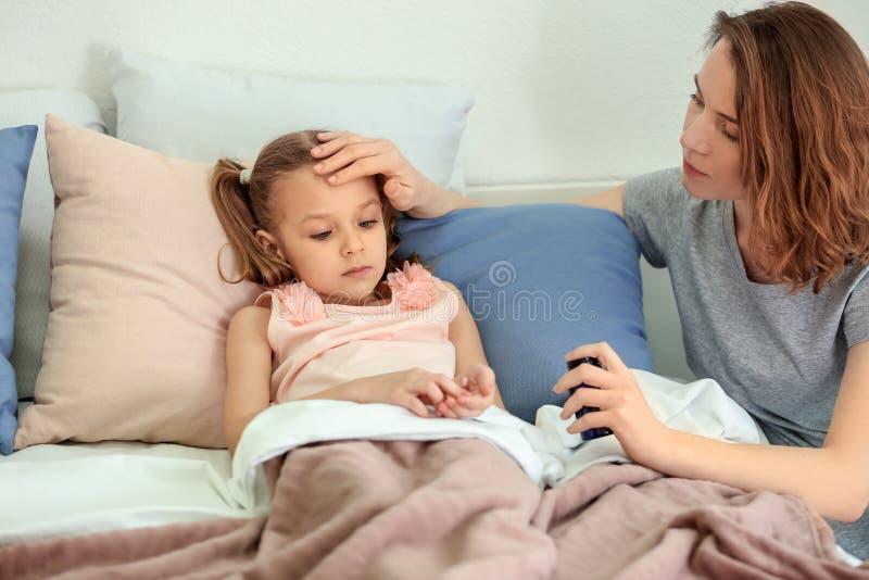 Giovane donna che dà pillola per sua figlia malata a letto fotografie stock libere da diritti