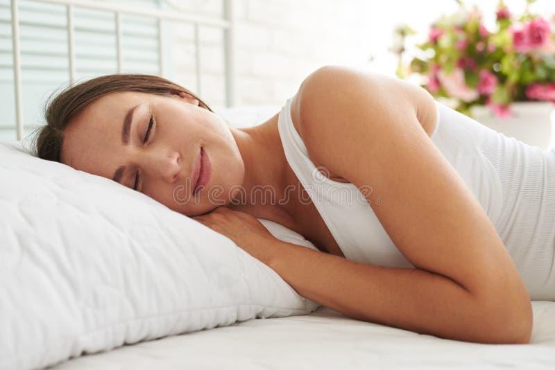 Giovane donna che dorme pacificamente nel suo letto che affronta alla macchina fotografica immagine stock