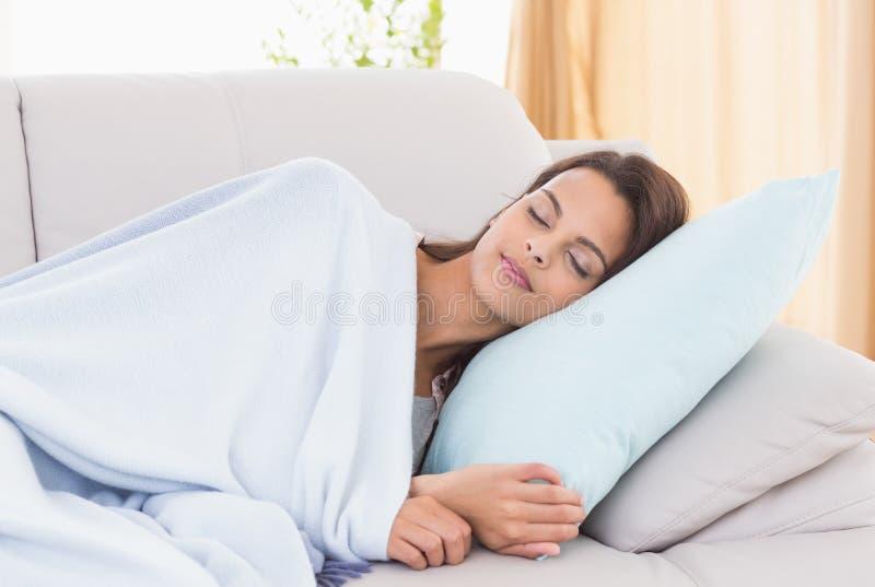 Giovane donna che dorme sul sofà immagini stock libere da diritti