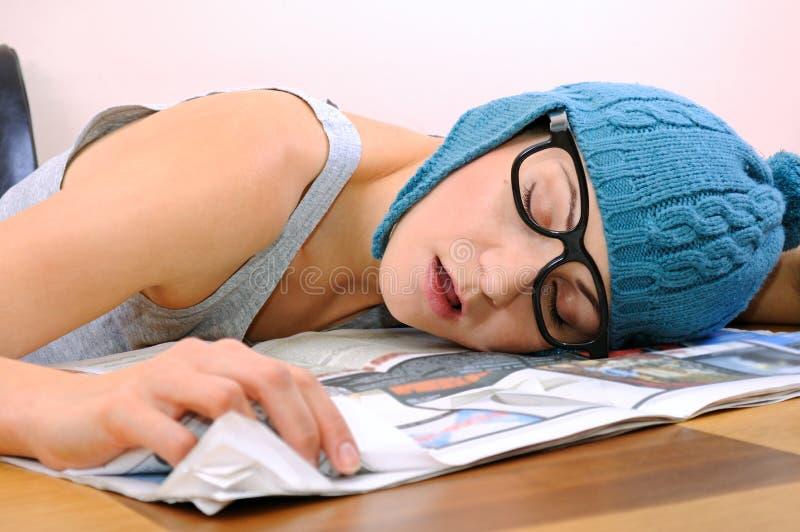 Giovane donna che dorme sulla tabella immagine stock