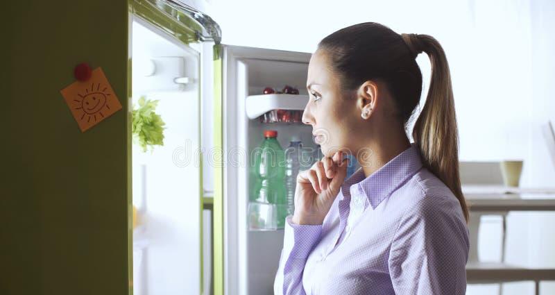 Giovane donna che esamina il frigorifero fotografia stock