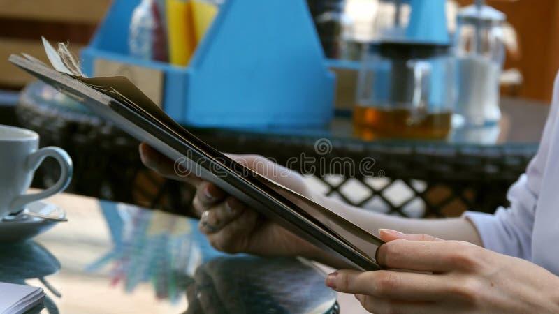 Giovane donna che esamina il menu in un ristorante immagine stock