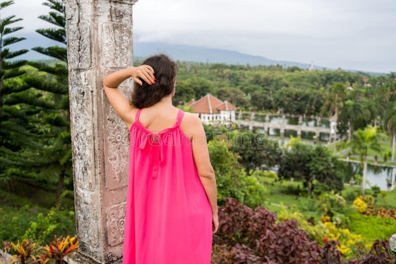 Giovane donna che esamina paesaggio del parco di Ujung del palazzo dell'acqua di Ujung o del parco di Sukasada su Bali, Indonesia fotografia stock libera da diritti