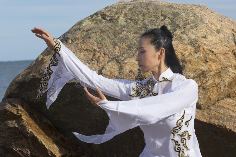 Giovane donna che esegue il gong di Qi su una spiaggia rocciosa di Connecticut immagini stock