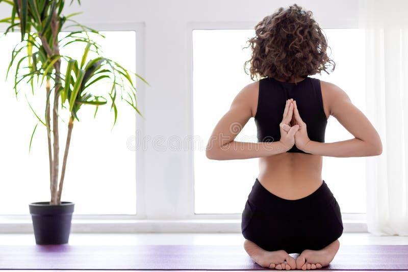Giovane donna che fa allenamento di yoga a casa immagini stock