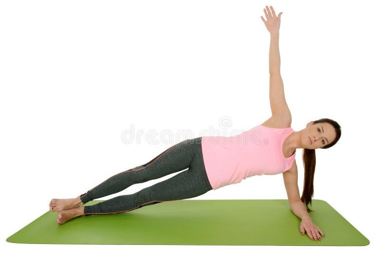 Giovane donna che fa asana Vasisthasana, sponda di yoga immagine stock