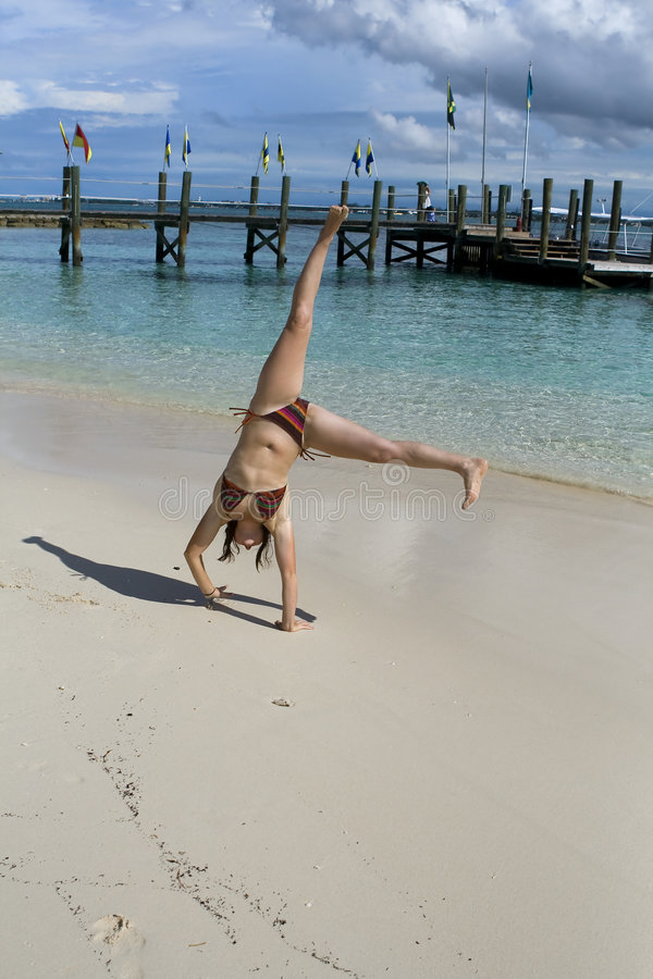 Giovane donna che fa cartwheel sulla spiaggia tropicale fotografie stock libere da diritti