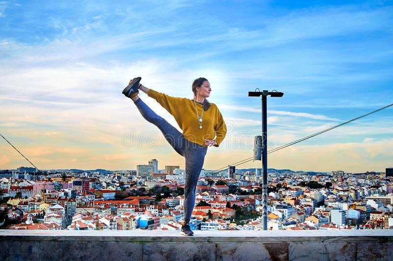 Giovane donna che fa esercizio di yoga all'aperto sui precedenti di vista della città di Lisbona immagini stock libere da diritti