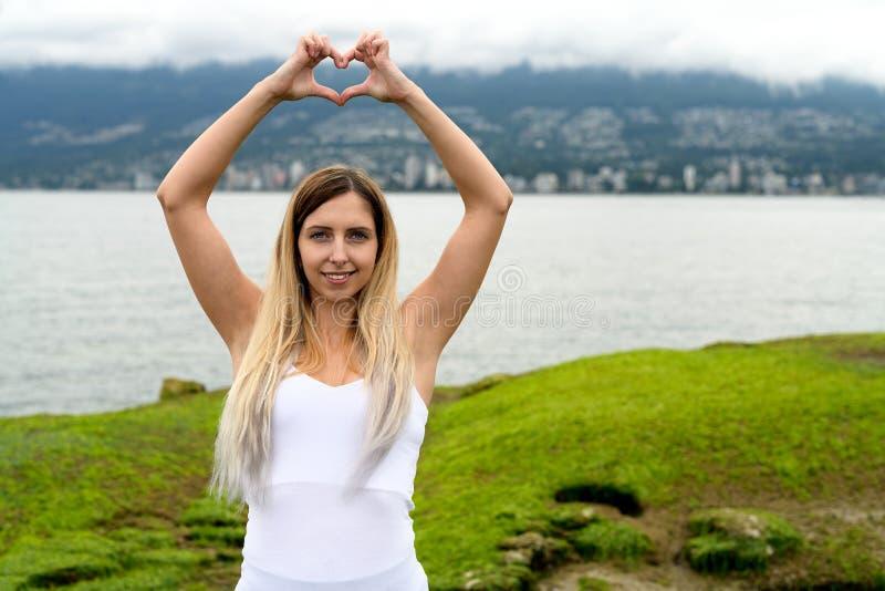 Giovane donna che fa forma del cuore con le mani in agai della città di Vancouver immagini stock libere da diritti