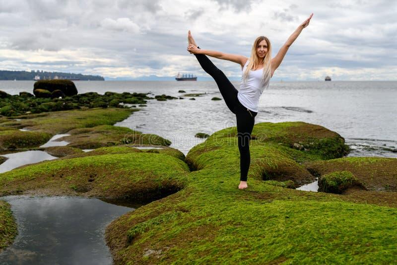 Giovane donna che fa gli esercizi acrobatici alla zona intercotidale di immagini stock