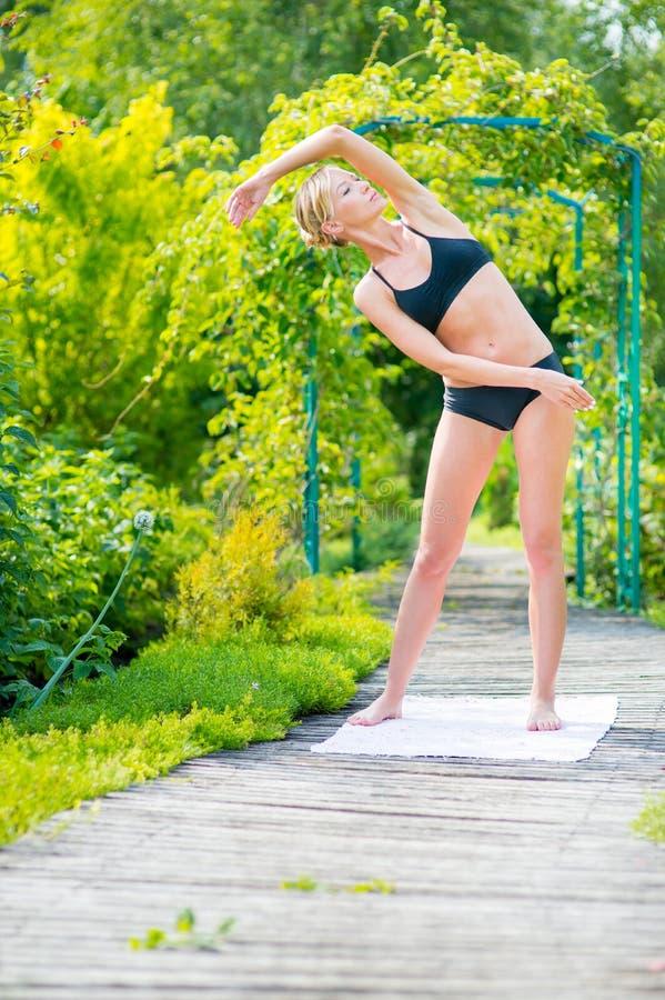 Giovane donna che fa gli esercizi nel parco un giorno soleggiato Forma fisica immagini stock