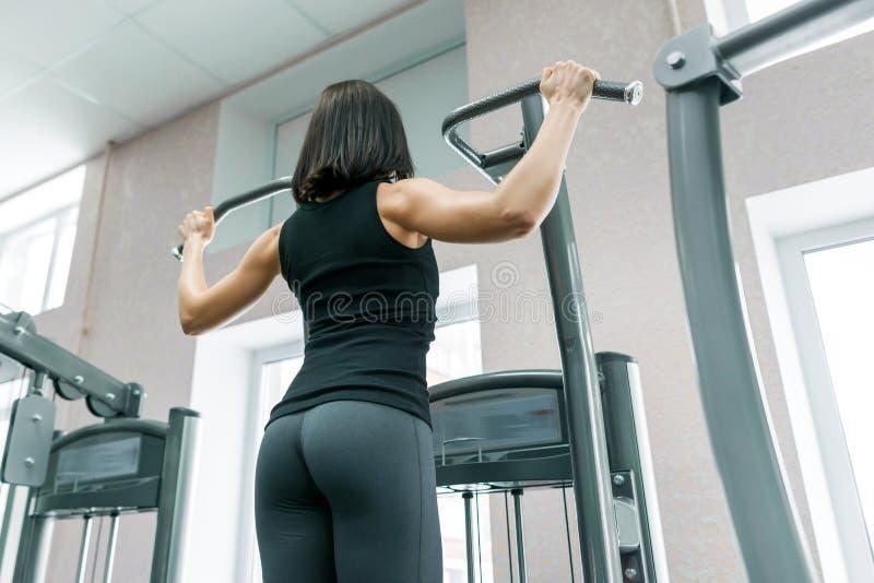 Giovane donna che fa gli esercizi per la parte posteriore su una macchina di forma fisica nella palestra, vista dalla parte poste immagini stock libere da diritti
