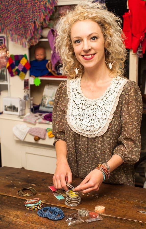 Giovane donna che fa i gioielli del braccialetto fotografia stock