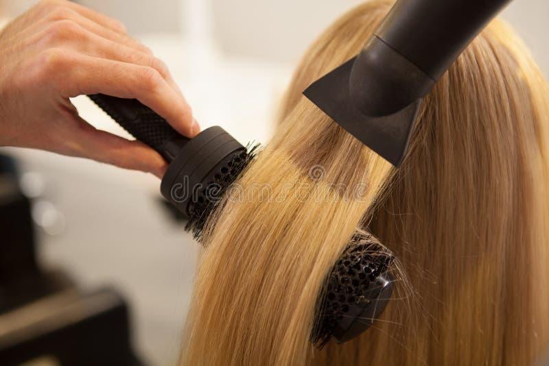 Giovane donna che fa i suoi disegnare capelli dal parrucchiere immagini stock libere da diritti