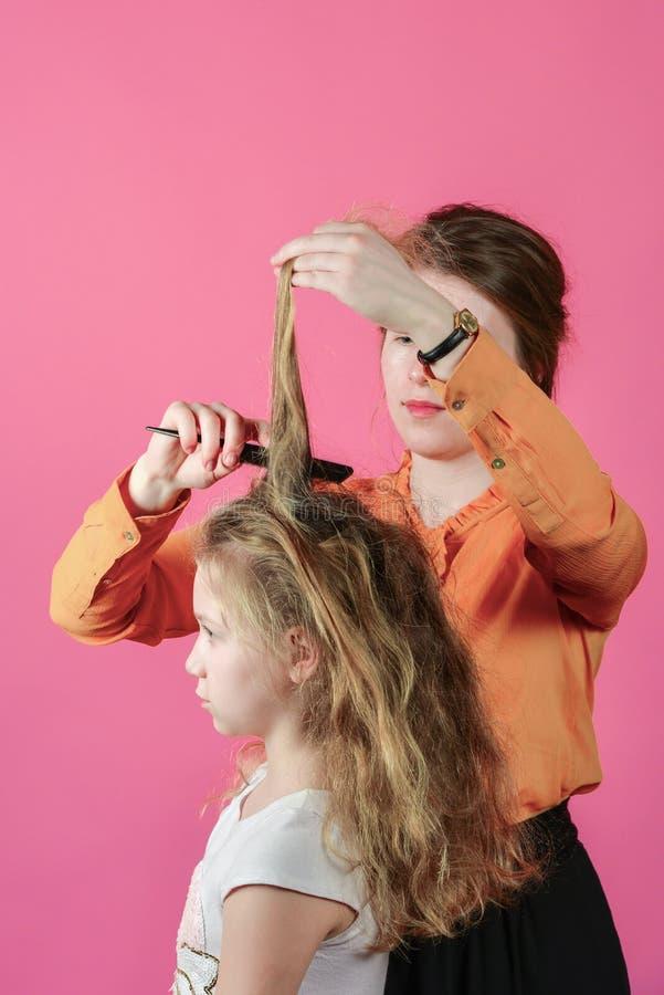 Giovane donna che fa la ragazza dell'acconciatura, nello studio su un fondo rosa fotografia stock