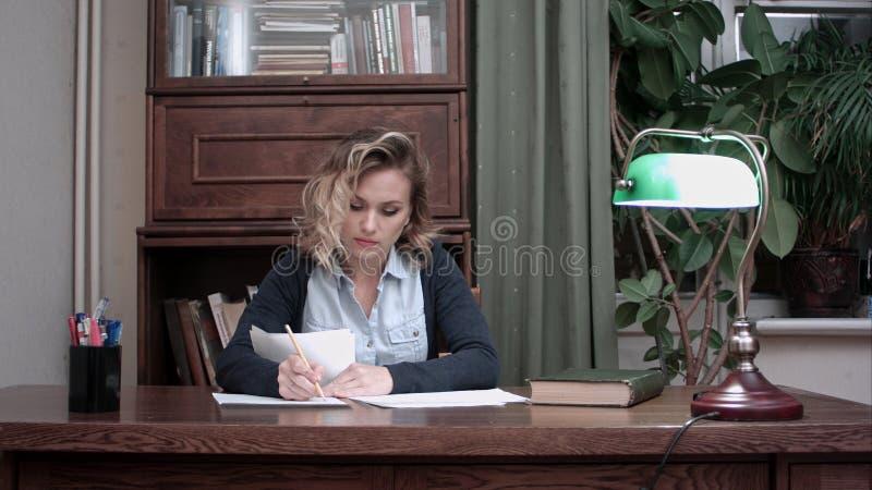 Giovane donna che fa lavoro di ufficio nell'ufficio che si siede al suo scrittorio fotografia stock