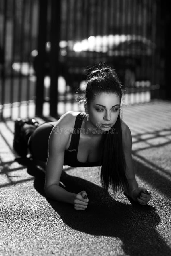 Giovane donna che fa plancia all'aperto fotografia stock