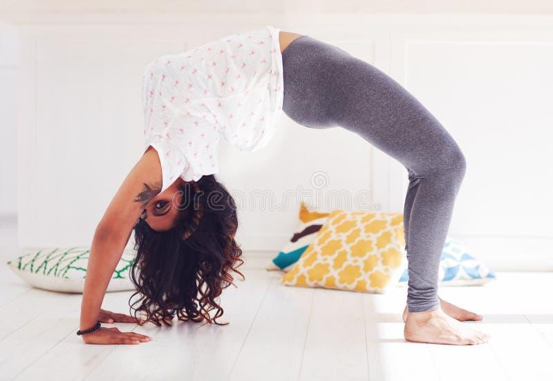 Giovane donna che fa posa completa della ruota di yoga di Chakrasana a casa immagine stock