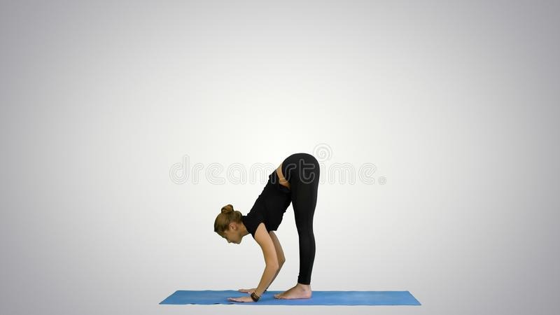 Giovane donna che fa posa yogic di saluto del sole sulla stuoia su fondo bianco fotografia stock libera da diritti